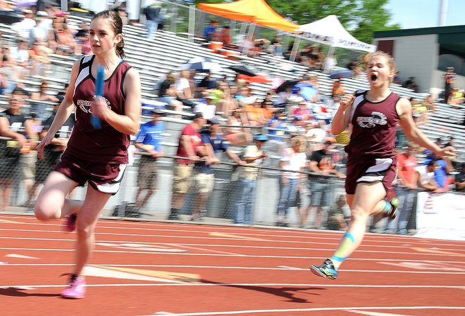 Soroco's Haley Johnson takes off with the baton as the Rams' Lauryn Bruggink cheers her Thursday during the first day of the state track meet in Lakewood. Soroco's 800-meter relay team advanced from the preliminary round to Friday's finals. After that race, the squad will join the three local athletes who won state medals in Thursday's action.