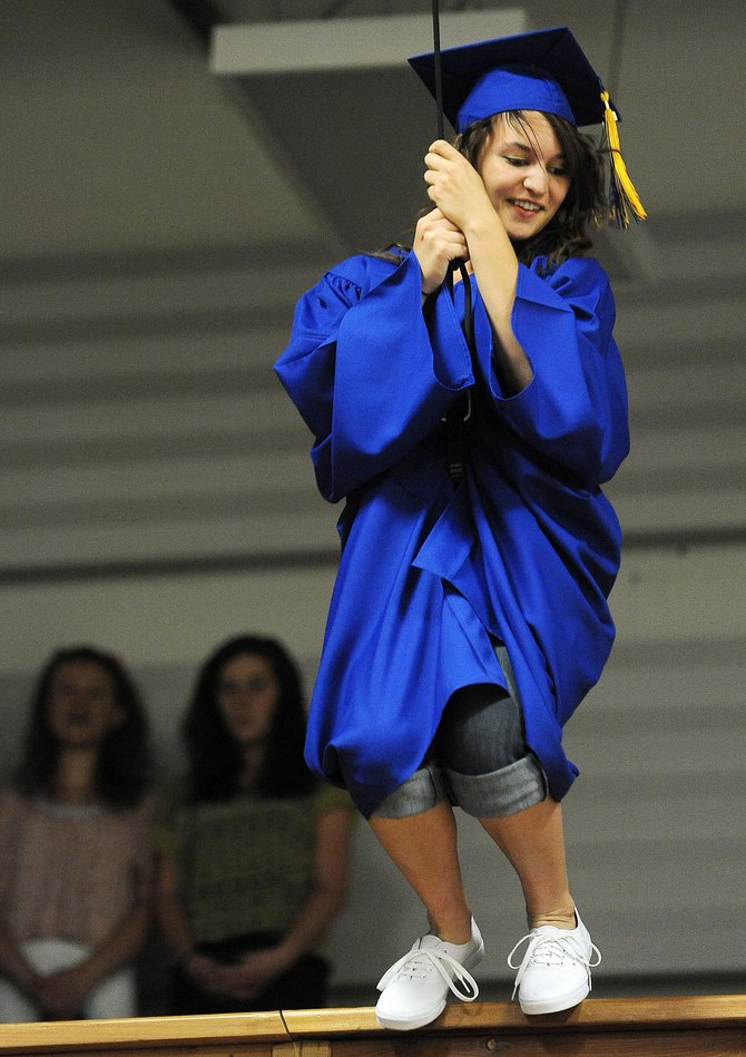 Victoria Belz prepares to jump off a balcony and slide into her graduation ceremony Sunday at Christian Heritage School in Steamboat Springs. The school's seven seniors rappelled into the ceremony.