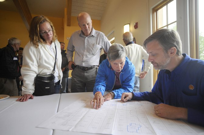 Hayden resident Tracey Rogalski and Steamboat Springs City Manager Jon Roberts watch as Steamboat resident Mary Littman speaks with Shell Oil's Matt Holman on Wednesday during an open house put on by Shell at the Steamboat Springs Community Center.