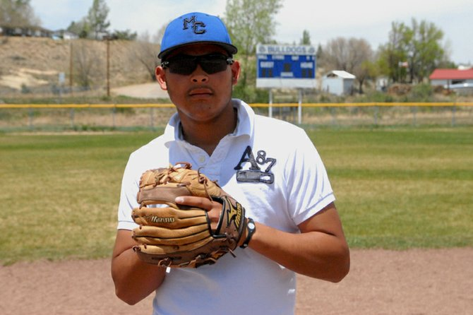 Moffat County High School senior and varsity baseball player Carlos Maldonado pounds his mitt at second base of the Craig Middle School baseball field. Maldonado was recently selected for the Under Armour Baseball Factory National Tournament Team, a summer program for players aged 14 to 18, and he will work with athletes in the Omaha National World Series in Nebraska in June.