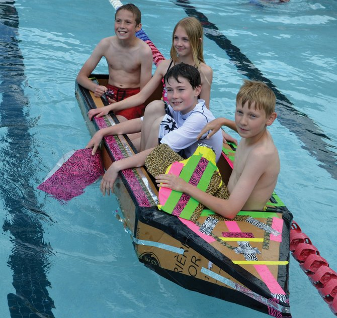 Soda Creek Elementary School fifth-graders Addison Sandvik, from right, Charles Leech, Madeline Brusky and Eric Casey aboard their winning craft, the Cinatit.