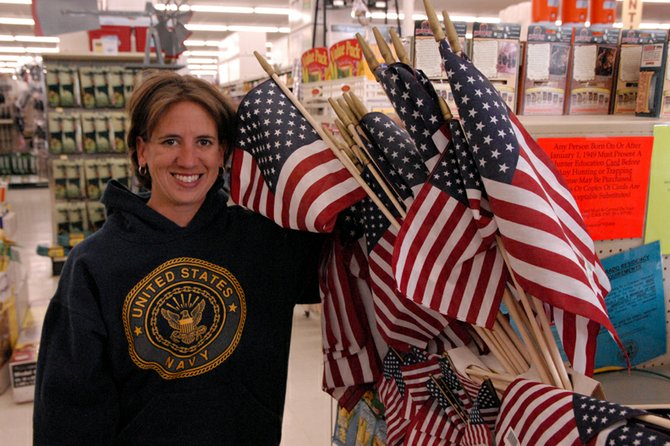 Mandy More shows off the patriotic setup of miniature American flags on sale at Murdoch's. More, 30, is an assistant manager at the supply store and will be paying tribute to members of the military today, including her grandparents and her sister, who recently finished a tour of duty with the U.S. Navy.