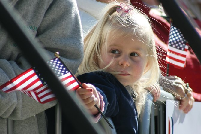 A young girl holds a flag during a campaign rally Tuesday morning for Republican presidential nominee Mitt Romney. About 2,000 people, or more by some estimates, attended the event at Alice Pleasant Park in downtown Craig.