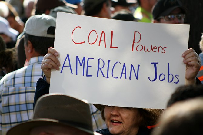 Dianna Orf, of Denver, holds a sign Tuesday morning before the Mitt Romney rally at Alice Pleasant Park. Orf does freelance work with the American Coalition for Clean Coal Electricity, Colorado Mining Association and Association of Governments of Northwest Colorado.