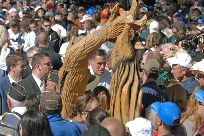 GOP presidential nominee Mitt Romney stands behind a Whittle the Wood Rendezvous sculpture as he makes his way through the crowd Tuesday morning at Alice Pleasant Park in downtown Craig.