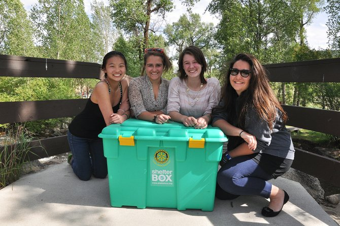 Steamboat Springs High School exchange students, from left, Kestral Johnston, Mallory Richey, Hope Nelson and Deniz Buyukbaykal pose with a ShelterBox on Wednesday near Bud Werner Memorial Library. Proceeds from a silent auction Friday at Steamboat Bean Coffee Co. will go toward purchasing one of the boxes that can support a displaced family of four for a year.