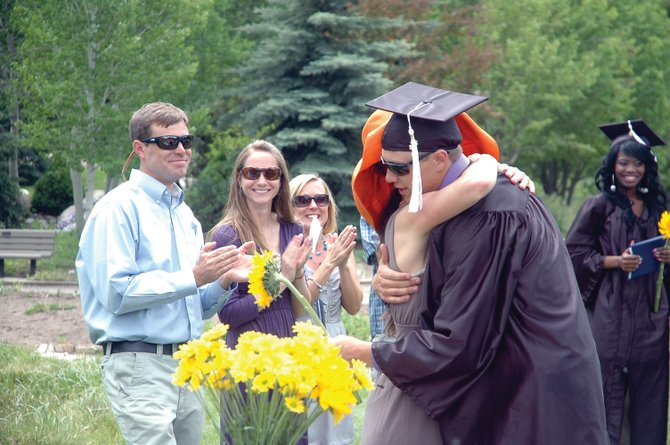 Gaven Van Pelt receives his diploma from Yampa Valley High School counselor Molly Lotz during graduation Friday at Yampa River Botanic Park. The alternative high school graduated five seniors this year.