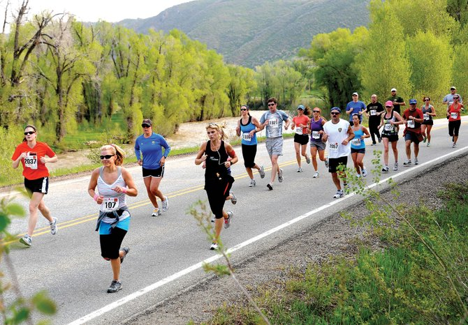 Cassie Dean, No. 107, of North Carolina, runs in front of a stream of half-marathon runners June 5, 2011, during the Steamboat Marathon in Steamboat Springs. About 1,700 runners are expected to participate in this year's event Sunday.
