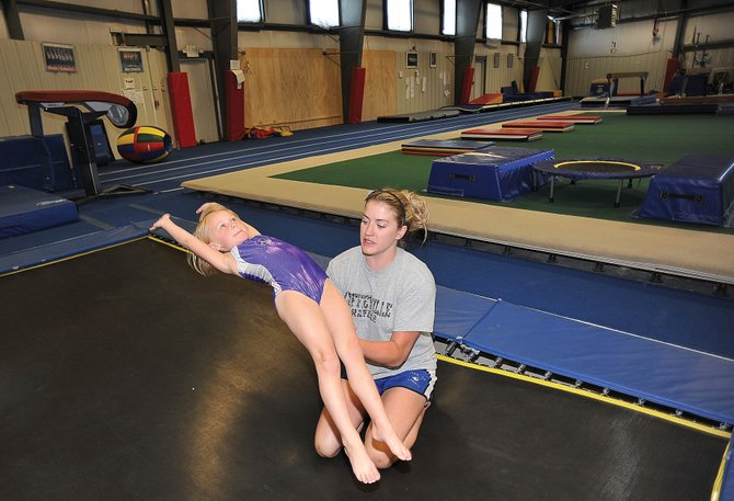 Gymnastics coach Kim Jones works with 4-year-old student Finley Danielson on Friday morning at Excel Gymnastics in Steamboat Springs.
