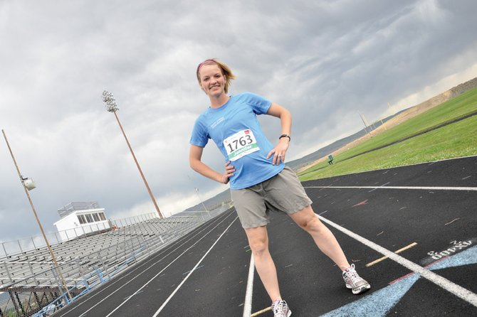Moffat County High School cross country coach Jennifer Pressgrove stands on the MCHS track wearing her bib from the 2012 Steamboat Marathon half marathon race. Pressgrove completed the race in 1:39:02 and was the 11th female to cross the line. It was her first half marathon in five years.