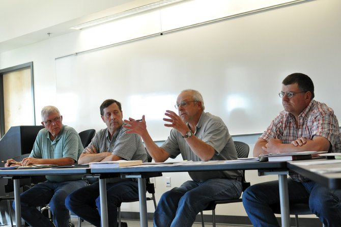 Rick Johnson, second from right, Colorado Northwestern Community College Board member, speaks during a special meeting Thursday about a proposed land transfer to the Craig Rural Fire Protection District for a fire training facility. The motion died for a lack of a second after about 15 community members voiced opposition to the proposed transfer.