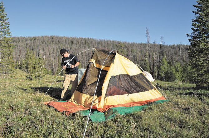 Eli Campbell demonstrates his ability to erect a Big Agnes tent solo Thursday evening during the Big Agnes/Honey Stinger/REI campout at Seedhouse Campground north of Clark. Campbell and his wife, Erin, had the tent on their wedding registry in 2010.