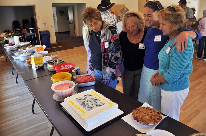Routt County Pioneer Picnic attendees from left, Carol Stehley, Beverley Lehrer-Brennan, Candice Bannister and Julie Solley admire a cake Sunday decorated with a picture of an early Routt County pioneer picnic taken in 1900.
