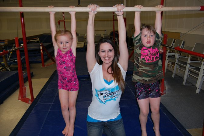 Jordan Porter, center, hangs out on the uneven bars at Gymstar Fun N Fit Gymnastics with students Heidi Snow, 4, left, and Arianna Anderson, 6. Porter, 18, is an instructor for the business and has participated in gymnastics most of her life. A 2012 Moffat County High School graduate, she will attend the University of Northern Colorado in the fall and plans to become a preschool teacher.