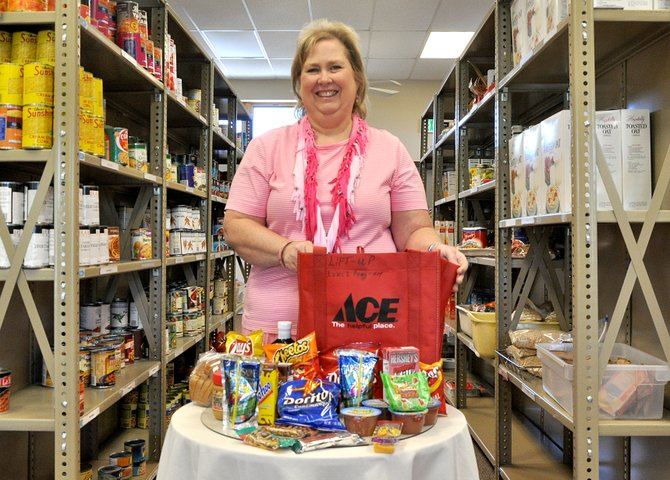 LIFT-UP of Routt County food bank and case manager Sherri McKnight poses with a bag of food that will be given to a child of a low-income family. LIFT-UP of Routt County and Totally Kids have launched free summer lunch programs to combat child hunger.