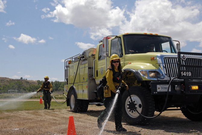Bureau of Land Management firefighters Jamie Geerdes, front, and Jeremiah Taylor practice mobile attack skills during a two-day wildfire orientation in May at Loudy-Simpson Park in Craig. The training event was organized by the Northwest Colorado Fire Management Unit, of which Moffat County is a member.
