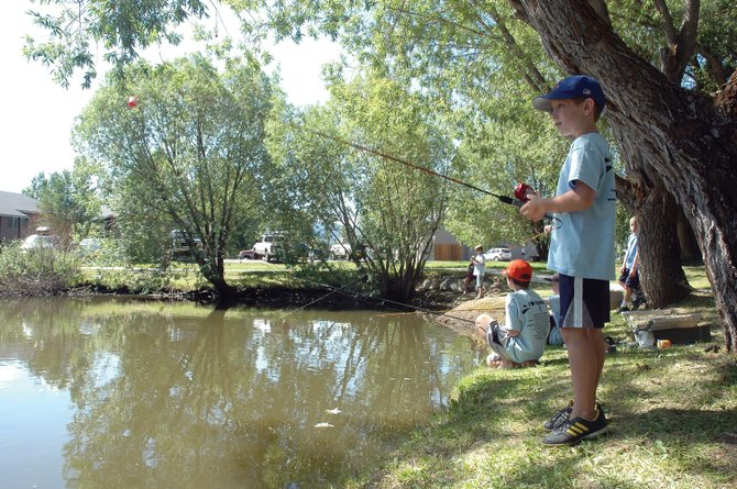 Adrian Bowman, 8, eagerly awaits a bite on his line Saturday at Walton Pond during the 30th annual Fishing Derby organized by the Optimist Club of Steamboat Springs. Eighty-five children participated in the event, catching 43 fish total.