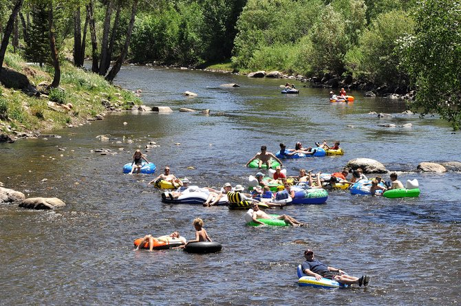 Clusters of tubers float down the Yampa River on Sunday near the Fifth Street Bridge. The river was barely flowing above 100 cubic feet per second Sunday afternoon, and its decline is expected to continue as hot dry weather is in the forecast again this week.