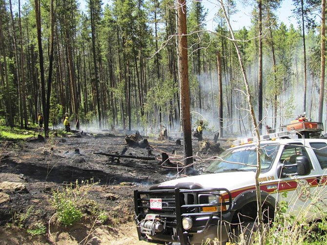 Oak Creek Fire Protection District firefighters work at a lightning-caused wildfire Monday southwest of Oak Creek on U.S. Forest Service land.