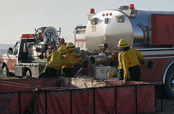 Craig Fire/Rescue firefighters refill Tender 1 with water before heading back out to battle a wildfire about 10 miles west of Craig. The water in the portable tank was trucked in by Herod Industries, Inc. employees who saw the blaze and offered firefighters their assistance.