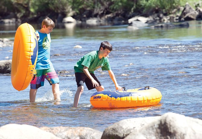 Tubers Ashtyn Franks and Landon Pollock wade into the waters of the Yampa River on Thursday to escape the heat in Steamboat Springs. Colorado Parks and Wildlife and city of Steamboat Springs officials Thursday afternoon asked everyone to stay out of the Yampa as it continues to flow below 85 cubic feet per second.