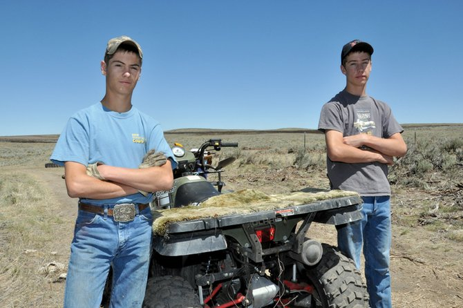 "Tyler Gerber, 15, left, and his brother Kearn, 14, stand near a four-wheeler they used Wednesday to repair fence on the family ranch after Tuesday's Sand Fire about 10 miles west of Craig. Tyler saw the blaze soon after it ignited, and he was ""praying that it wouldn't get on our place, but that didn't happen,"" he said. The fire blackened parts of their grazing land but did not damage the family's home."
