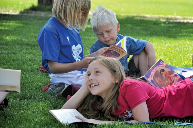 "Alexa Neton, 9, center, talks with a friend Tuesday at Veterans Memorial Park while her brother, Patrick, 4, reads with Emma Jones, 8. They were among about 75 elementary school students who attended ""Light Your Fire for Reading,"" the first of three activities to encourage children to read during the summer."