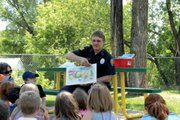 Firefighter Matthew Walker, of Craig/Fire Rescue, reads to a group of children Tuesday in Veterans Memorial Park as part of Light Your Fire for Reading, an event designed to encourage children to read during the summer. Other reading events take place at 5 p.m. July 10 at the Craig Swimming Complex, 605 Washington St., and from 1 to 4 p.m. Aug. 14 at Colorado Northwestern Community Colleges Craig campus, 2801 W. Ninth St.