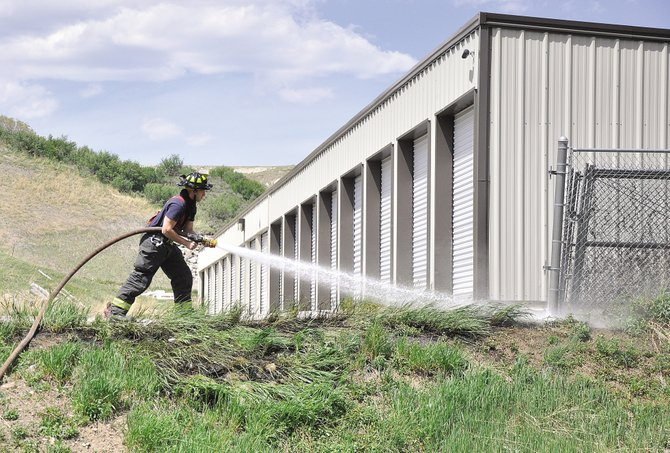 Steamboat Springs Fire Rescue firefighter Devin Borvansky sprays water on a small grass fire on the west end of Steamboat Springs in May. Steamboat's firefighters will be the second-largest beneficiary of pay raises approved Tuesday by Steamboat Spring City Council.