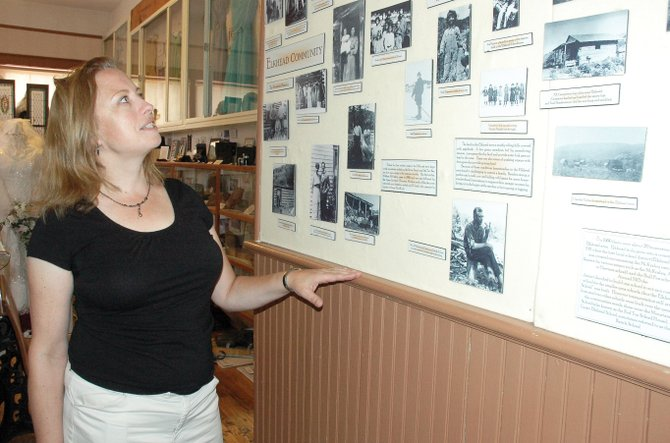 Laurel Watson, curator of the Hayden Heritage Center, points out photos in an exhibit featuring the Elkhead community. A tour of the Elkhead Schoolhouse will be part of Hayden Heritage Days next weekend.