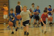 Boys from fourth through eighth grade dribble down the court to work on ball-handling skills. The Moffat County High School hosted a basketball camp Monday through today focusing on improving fundamentals. In the background, incoming MCHS sophomore Tyler Davis gets the next group of campers ready.