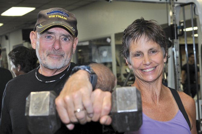 "Jim and Barb Gregoire pose for a photo together recently at Trapper Fitness Center, the business they co-own. Fitness and exercise also play a pivotal role in their life outside of work. Health is ""our passion,"" said Jim, 65."