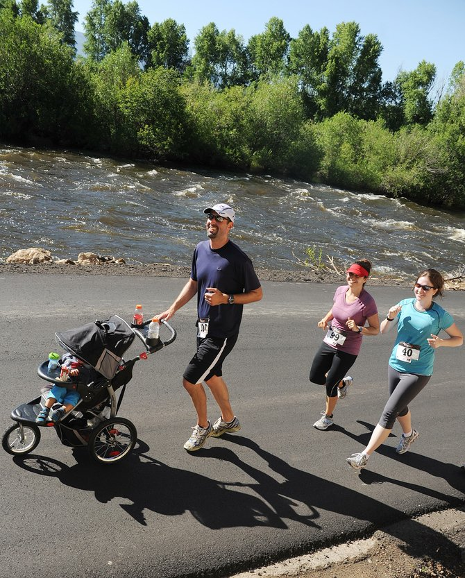 Runners head down River Road alongside a surging Yampa River during the 2011 Mountain Madness half-marathon and 10-kilometer race in Steamboat Springs. The scenery will be a bit different Sunday, when the race returns. The river is but a trickle, but a large field again is expected.