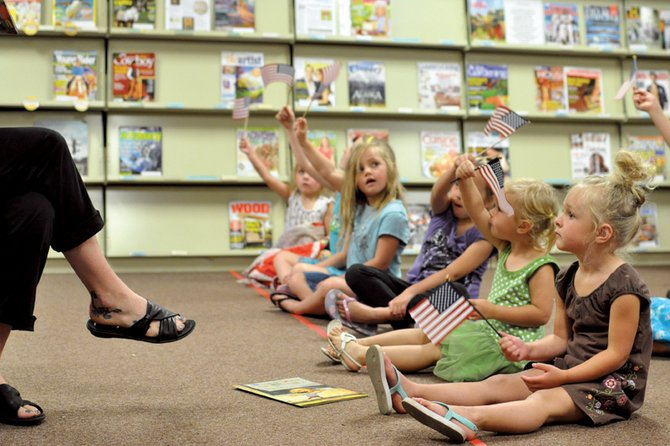 Meadow Simpson, 3, right, waves a flag with other children during a Independence Day-themed story-time Thursday at the Craig branch of the Moffat County Libraries. The weekly event is part of the library's summer reading program, which offers reading incentives for children, teens and adults.