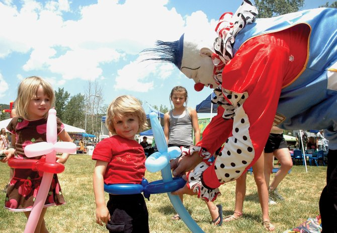 Jessica Houck, 5, watches as her brother, Finn, 3, gets a balloon sword just like hers from Jazz the Clown during Taste of South Routt on Saturday. The 15th annual Oak Creek festival drew hundreds to Decker Park for food, music, games and educational outreach.