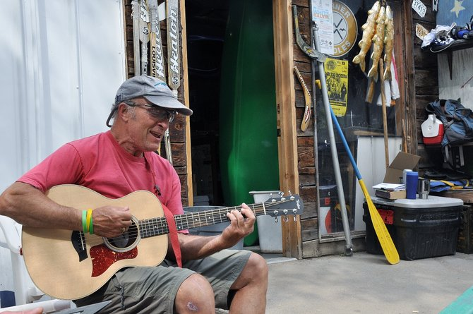 Pete Van De Carr plays his guitar Sunday to pass the time during another slow day at Backdoor Sports. Van De Carr and other river outfitters stand to lose tens of thousands of dollars this summer because of the Yampa River's closure, but they are adjusting to life after tubing.