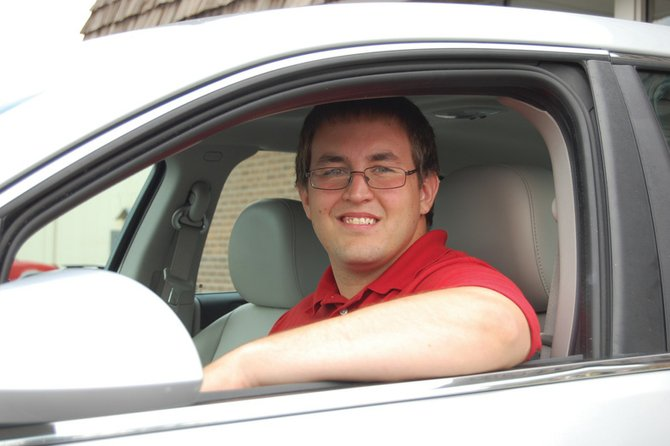 Austin Hill smiles behind the wheel of a newly sold Chevy in the car lot of Cook Chevrolet and Subaru. Hill, 21, started as a salesperson for the dealership in May. He and his wife recently celebrated their first anniversary.