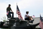 Veterans sit on top of Wyman Museums Korea-era M47 tank in Wednesdays Fourth of July Parade in Craig.