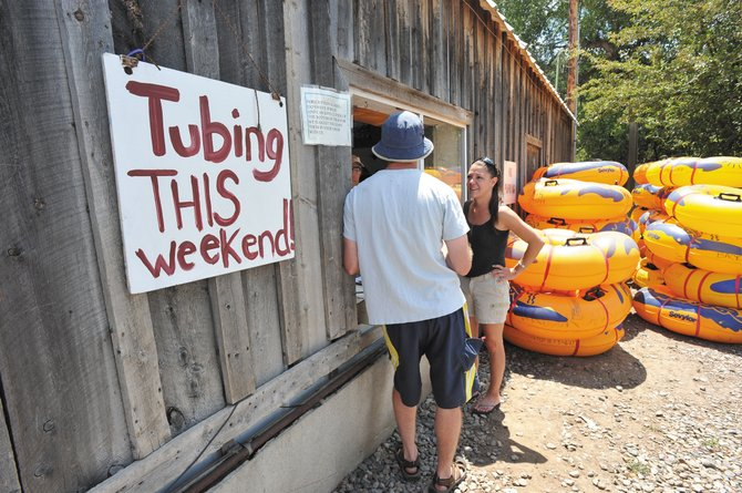 Derek Berglund, back to camera, and Janelle Samora, of Boulder, stopped by the tube rental window at Back Door Sports on Friday afternoon to ask about conditions before deciding if they wanted to go tubing on the Yampa River. The Yampa River rose above 85 cfs Friday allowing tubing to resume on the river as long as the flow remains above that level.