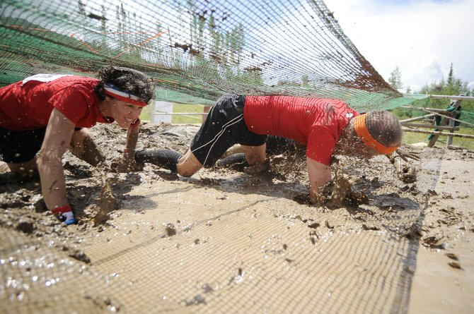 Kathy Elliott crawls through the mud pit during the Steamboat Mad Mud Run on Saturday at Steamboat Ski Area.