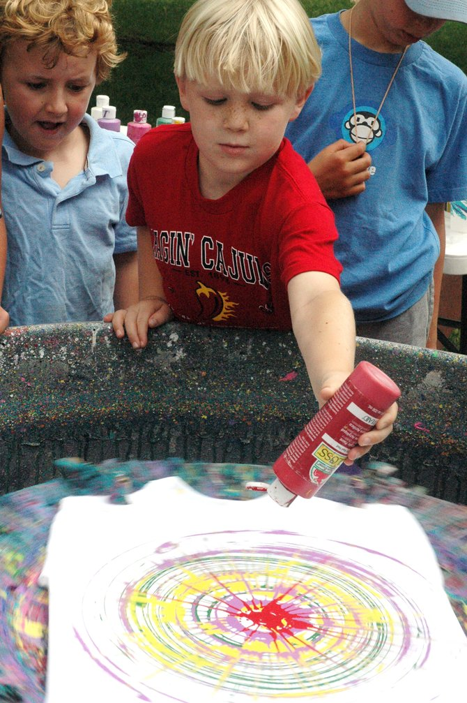 "Isaac Reiber, 7, creates a work of ""spin art"" at an Art in the Park booth run by locals Charlie and Gail Holthausen on Saturday in West Lincoln Park. The annual Steamboat Springs Arts Council event continues Sunday."