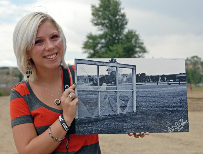 "Carli Griffith, an incoming Moffat County High School senior, poses with a print of ""Broken"" near the site of where she took the photograph at Loudy-Simpson Park in Craig. Griffith submitted the photograph to a Photographer's Forum contest. It was chosen as one of 600 finalists and is currently featured in the book Best of College and High School Photography 2012."
