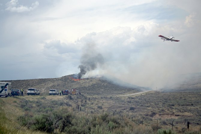 A plane flies over a wildfire Tuesday afternoon on Bureau of Land Management property off Moffat County Road 7. Firefighters from Craig Fire/Rescue, the Moffat County Sheriff's Office and the BLM responded to the fire along with an EMS crew from The Memorial Hospital.