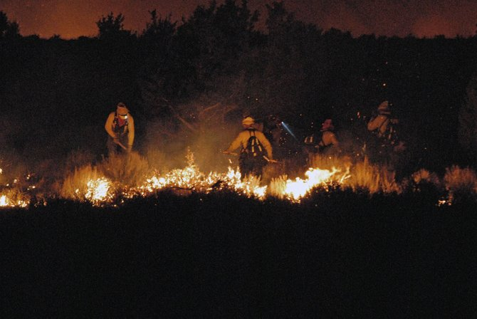 Bureau of Land Management firefighters backfire along Moffat County Road 59 South Tuesday night while battling the Cedar Knob Fire.