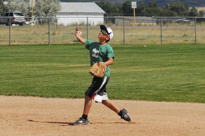 "Ulises Silva, 13, throws the baseball Thursday during a Moffat County Cutthroats practice. The Cutthroats are playing at the Triple Crown Baseball Colorado State Championships today and Saturday. Silva, an outfielder and team captain, says they are hoping to ""bring home a plaque and some medals."""