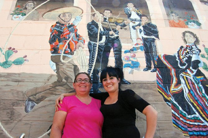 Sandra Loya, left, and employee Erika Reyes stand beneath the mural on the north wall of Loya's Mexican restaurant, Casa Loya, on its final day of business Thursday. Loya, who has owned and operated the establishment since 2001, is shutting down the eatery to focus on her family.