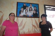 Sandra Loya, left, and Erika Reyes display the Loya family portrait before turning off the lights of Mexican restaurant Casa Loya for the final time. Loya, who has owned the business for the past 11 years, will rent the space to Double Barrel Steakhouse, formerly of Hayden, for the next year as she takes time off to focus on family.
