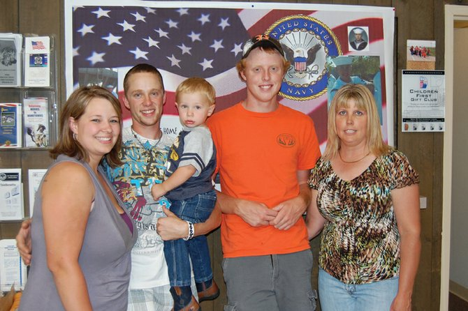 Jordan Bailey, second from left, stands proudly with wife, Kacie, son, Kaeden, cousin Wyatt Oberwitte and aunt Kathy Bailey beneath a banner made especially for him. Jordan recently returned from a tour of duty with the U.S. Navy and was greeted by friends and family at a surprise party Friday afternoon.