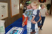 Jordan Bailey and his son, Kaeden, take a look at the cake made for Jordans homecoming party after spending several months overseas with the Navy. The picture of the father and son on the cakes frosting was taken before Jordan shipped out in November 2011.