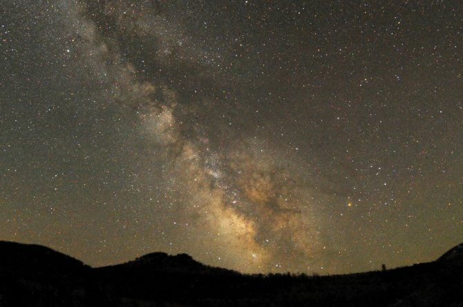 From a dark sky location, the summer Milky Way is stunning. In this time-exposure image, star clouds containing billions of distant suns are shown interspersed with tendrils of dark, obscuring dust and gas. The Milky Way, our home galaxy, is estimated to be about 80,000 light years across.